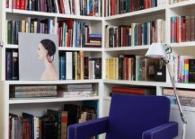Turning-the-small-corner-in-the-modern-Victorian-home-into-a-library-with-bright-pink-rug-blue-chair-and-ample-shelving-53608-217x155