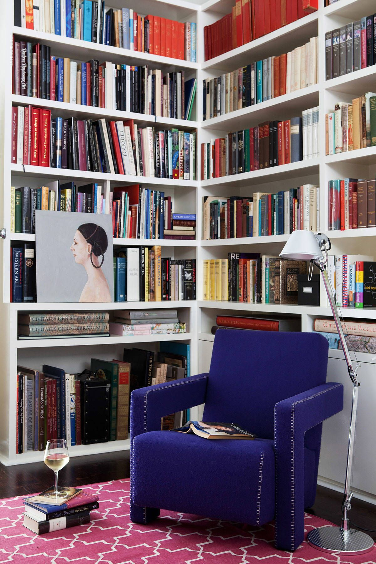 Turning the small corner in the modern Victorian home into a library with bright pink rug, blue chair and ample shelving