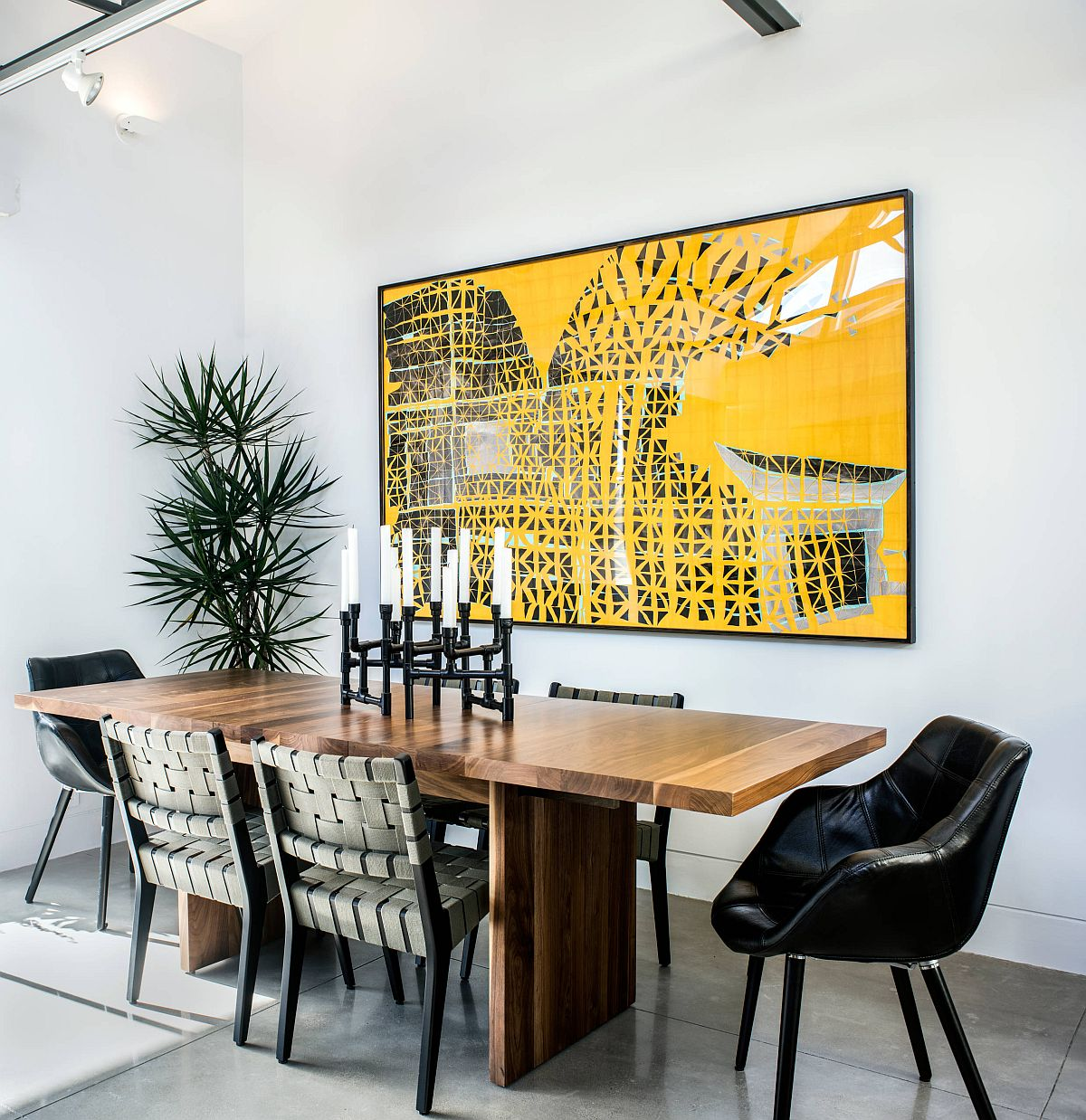Wall art in this dining room adds bright yellow to a black and white space