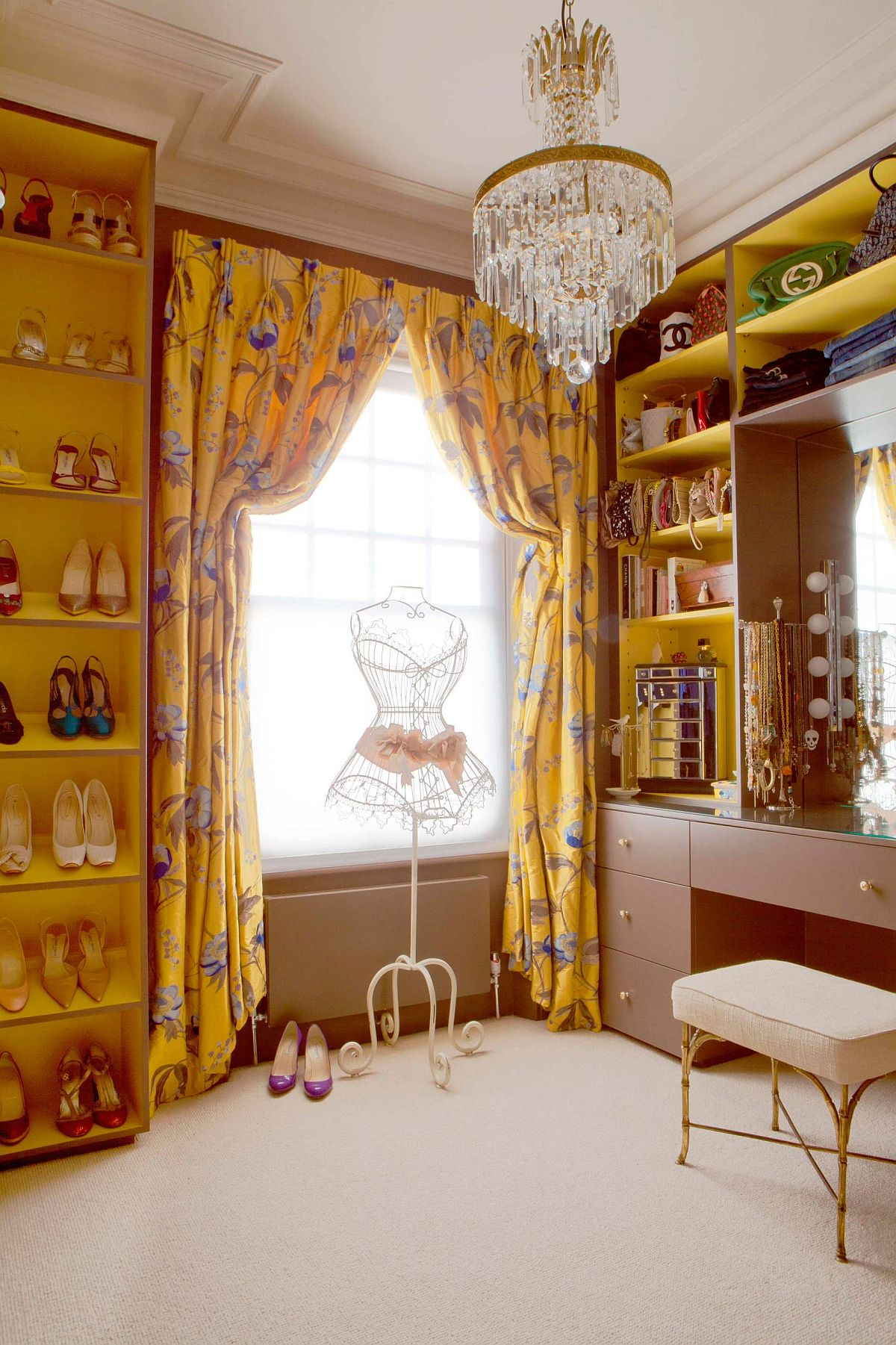 Yellow drapes and shelves bring color to this classic-eclectic walk-in closet with ample natural light