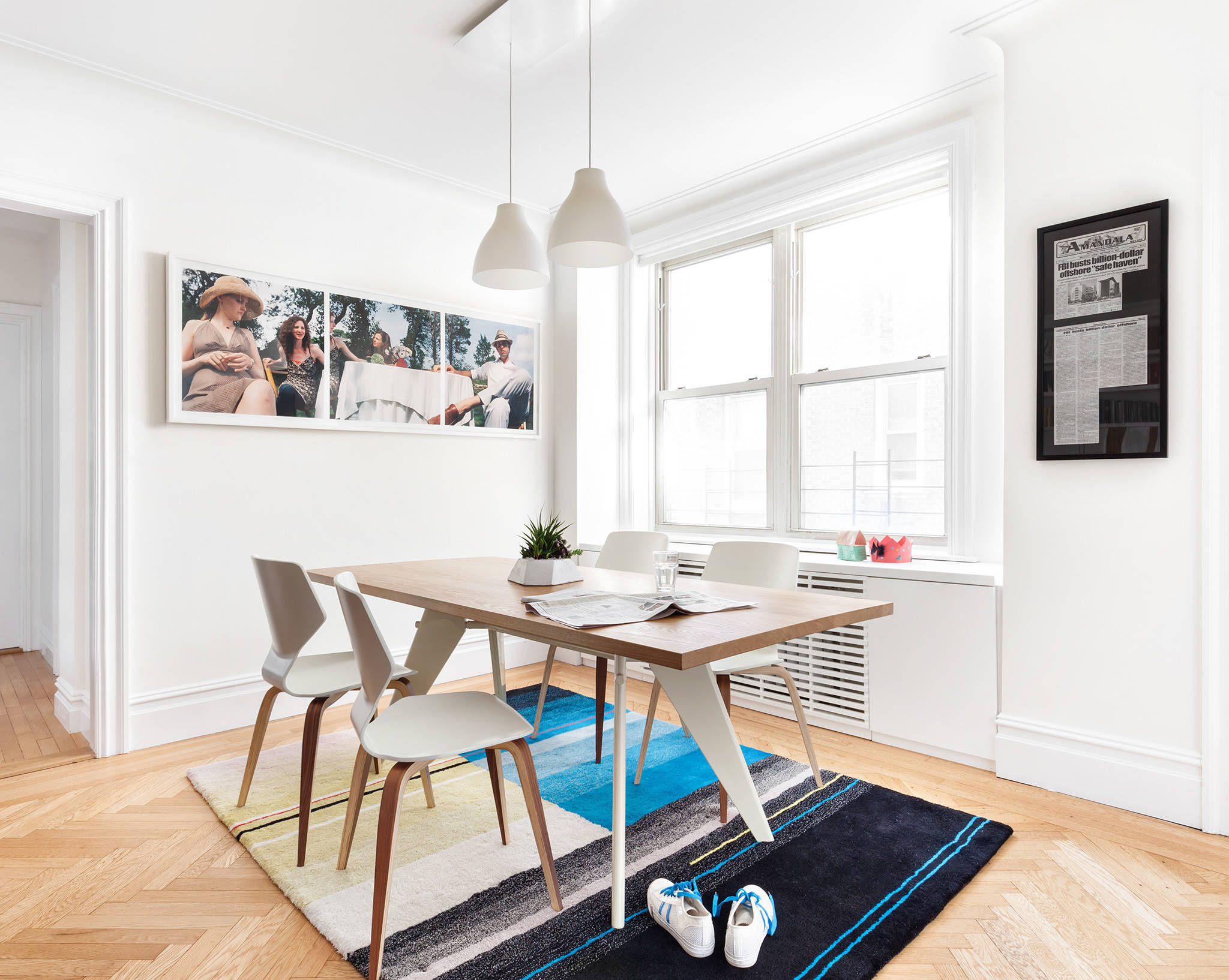 Add color to the small dining room in white with rug and wall art