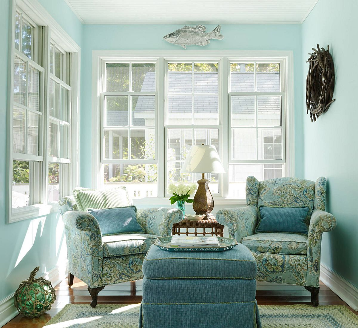 Beautiful beach style nursery in blue with relaxing club chairs and uncomplicated design