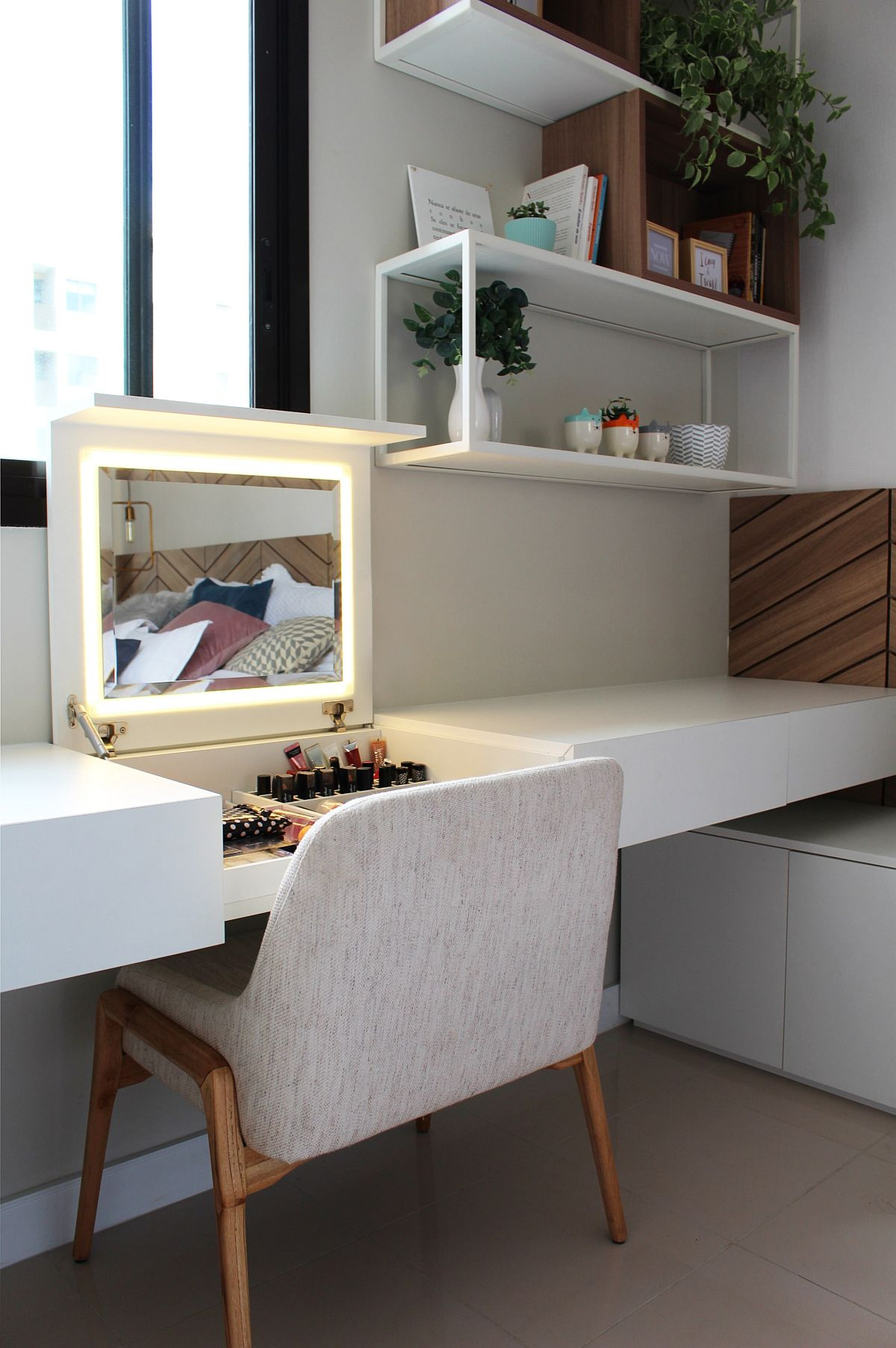 Bedroom study space along with storage units for beauty accessories and a space-savvy mirror
