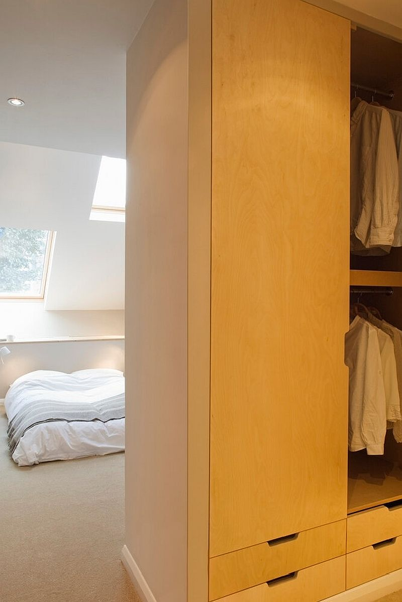 Bespoke wooden closets and wardrobes add storage space while delineating space inside the bedroom