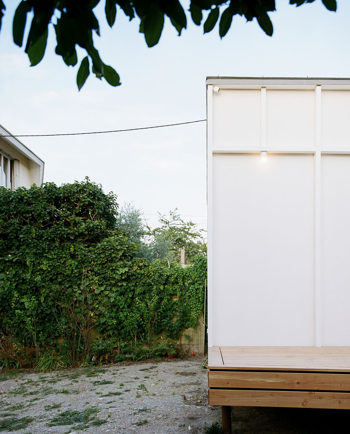 Box-styled rear extension of aging French home on an elevated wooden platform