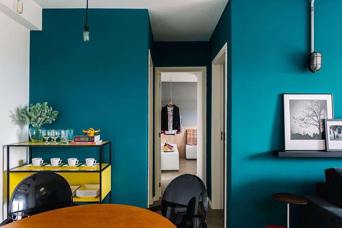 Bright blue walls create a vivacious apartment interior that feels fresh and modern