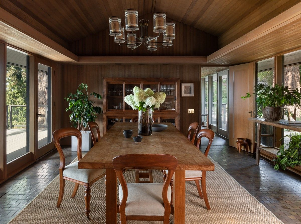 Cabin-style dining room of the house is connected with the outdoors using glass walls