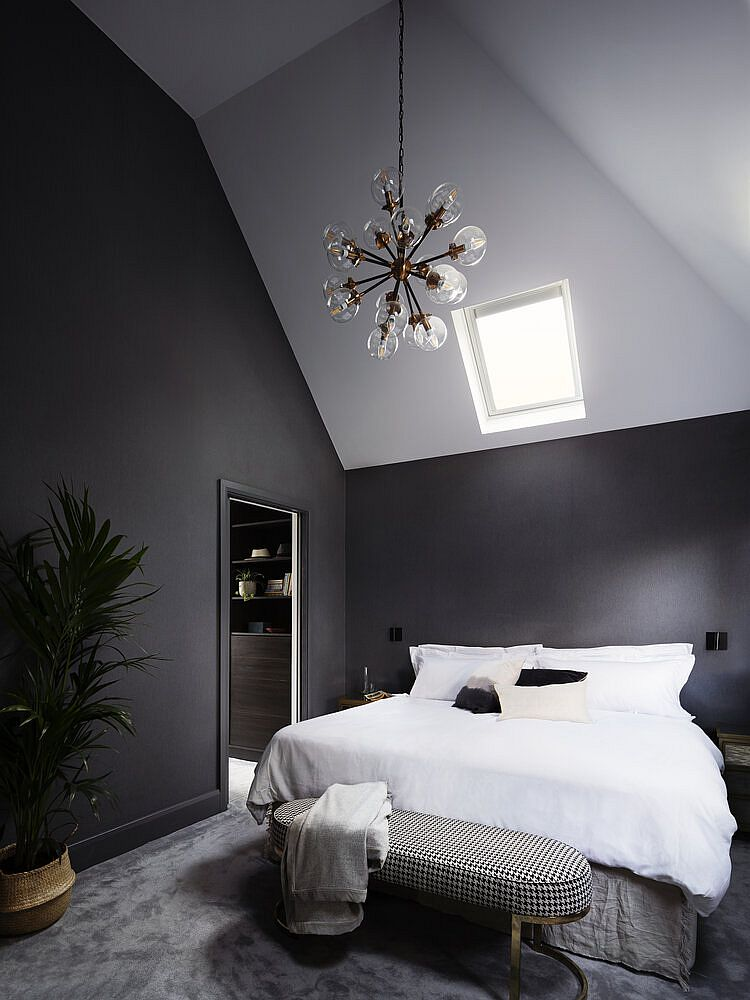 Chandelier adds a sense of dramatic elegance to this spacious master bedroom in gray