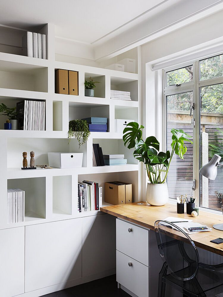 Curated and well-lit modern white home office with smart bookshlef and a wooden desk