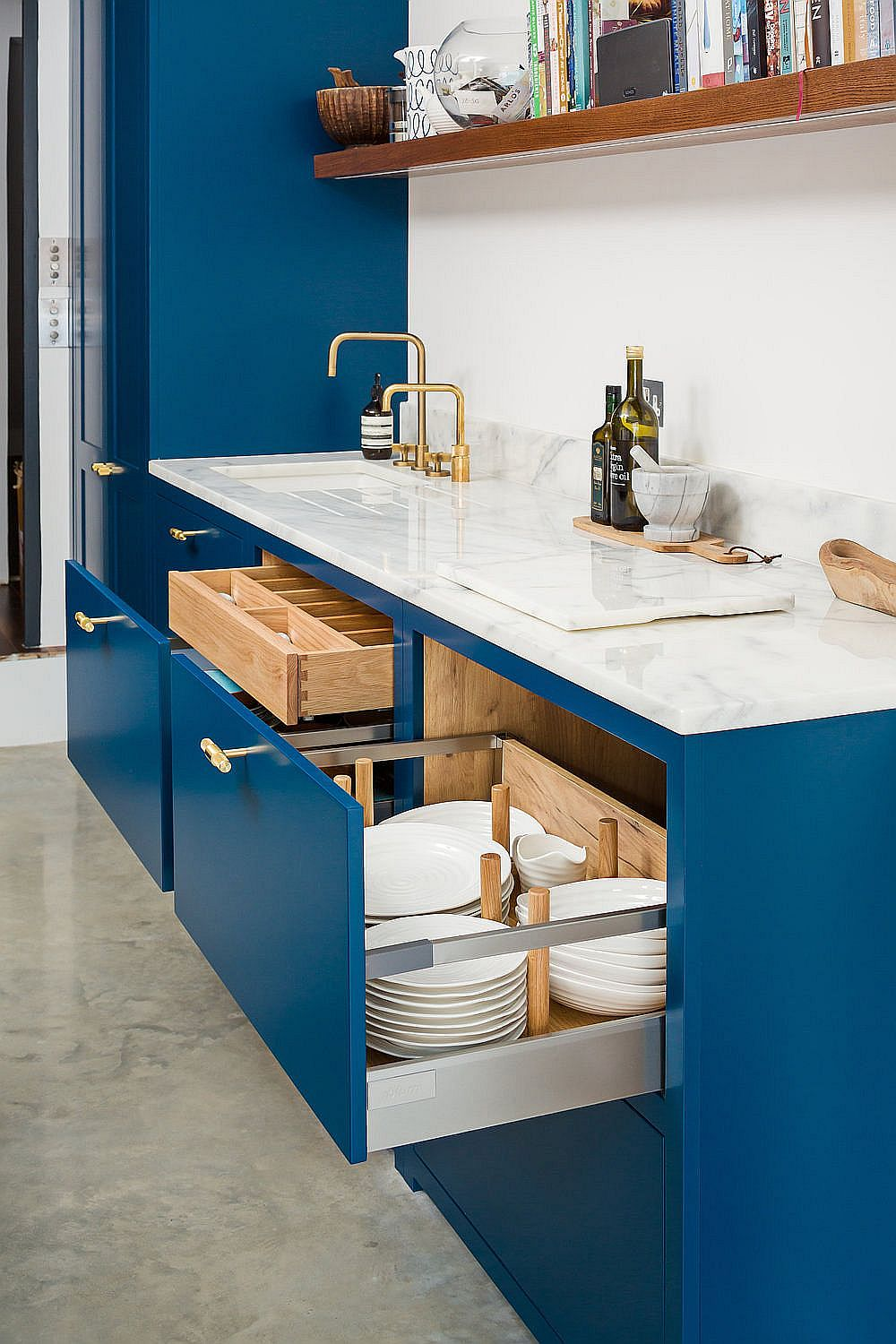 Custom designed workstation and drawers add to the functionality of this beautiful navy blue kitchen