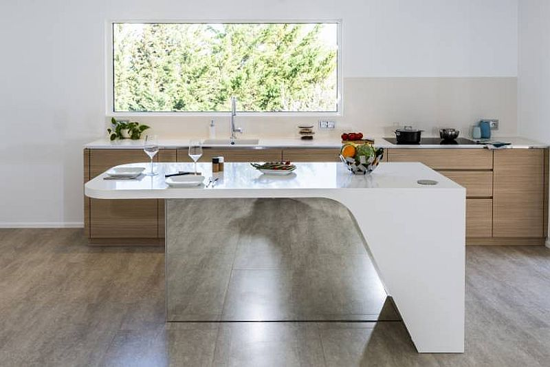 Custom kitchen island with a mirrored section and flowing form designed by Charlotte Raynaud and Menuiserie Hegenbart