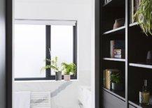 Dark-bookshelf-and-cabinets-in-wood-flank-the-corridor-leading-to-the-bathroom-43031-217x155