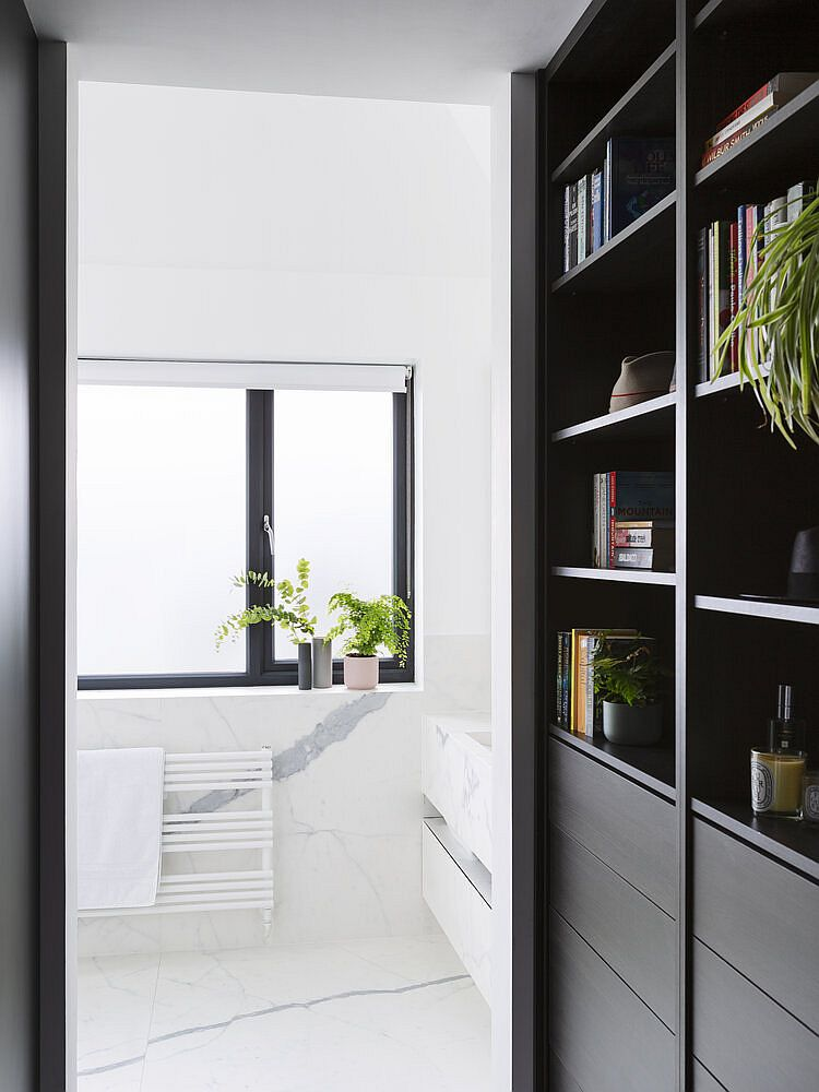 Dark bookshelf and cabinets in wood flank the corridor leading to the bathroom