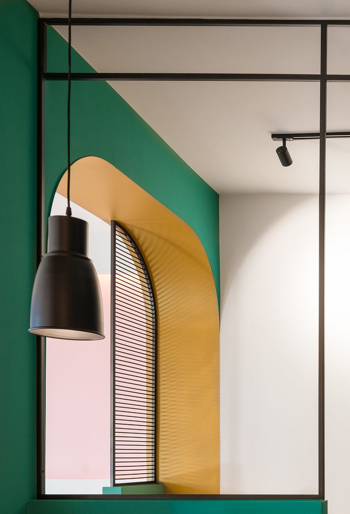 Dark green and bright yellow shape the backdrop of the apartmen while pops of black anchor it