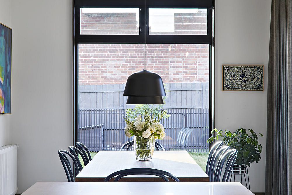 Dark pendants bring visual contrast to the contemporary dining space in neutral hues