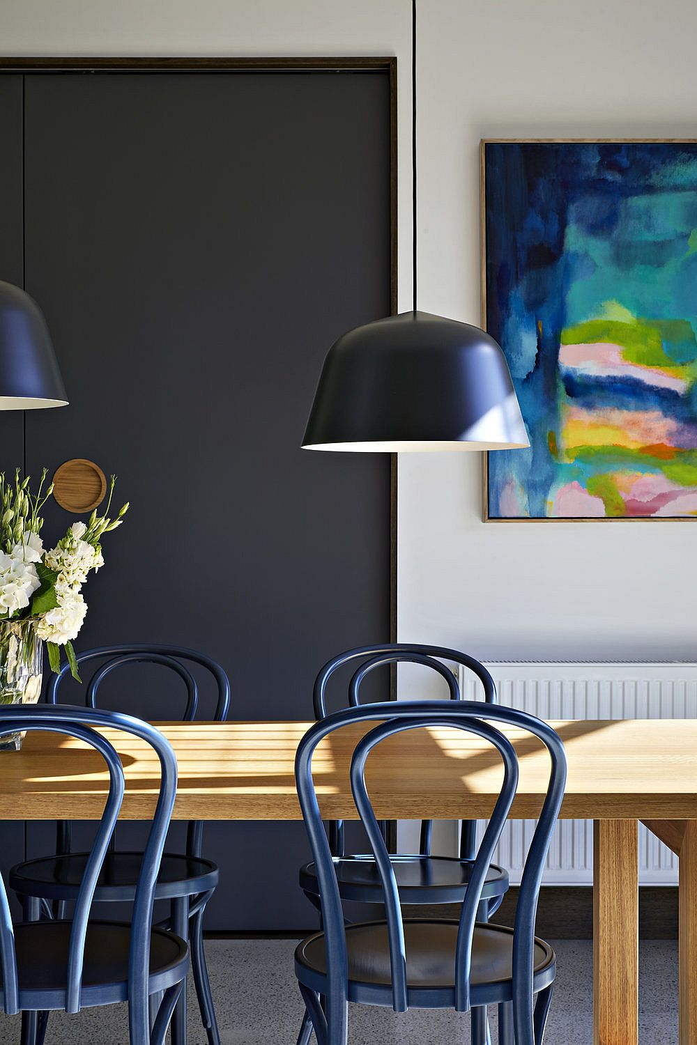 Dining table chairs, pendants and wall art add color to the contemporary neutral dining room