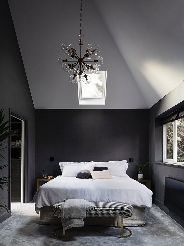 Double-height master bedroom in gray and white with sloped ceiling and skylights