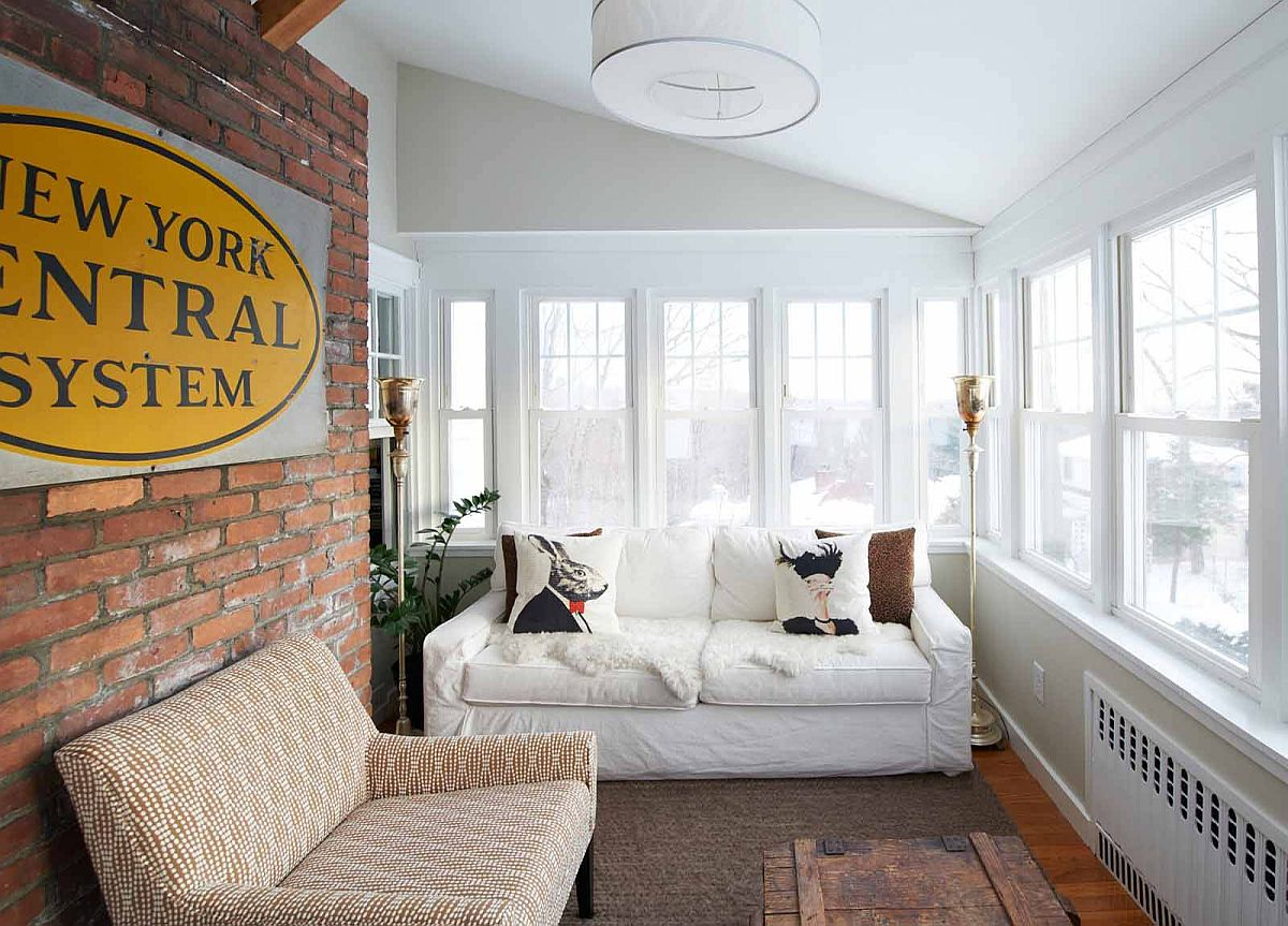 Exposed brick wall adds textural charm to the exquisite sunroom in white and wood