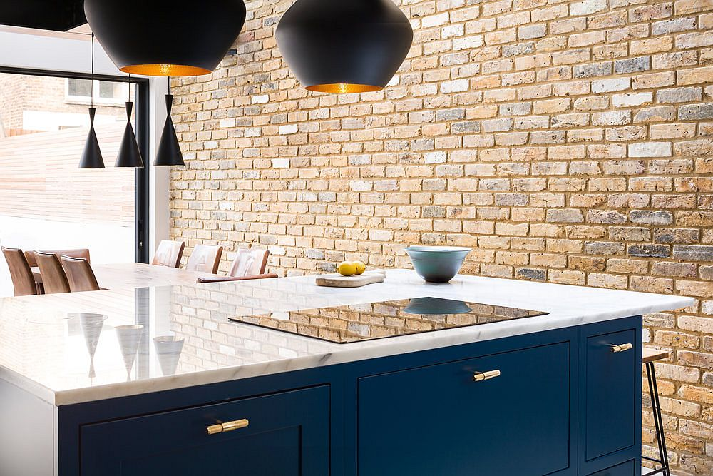 Exposed brick wall of the kitchen brings an industrial dynamic to the modern space