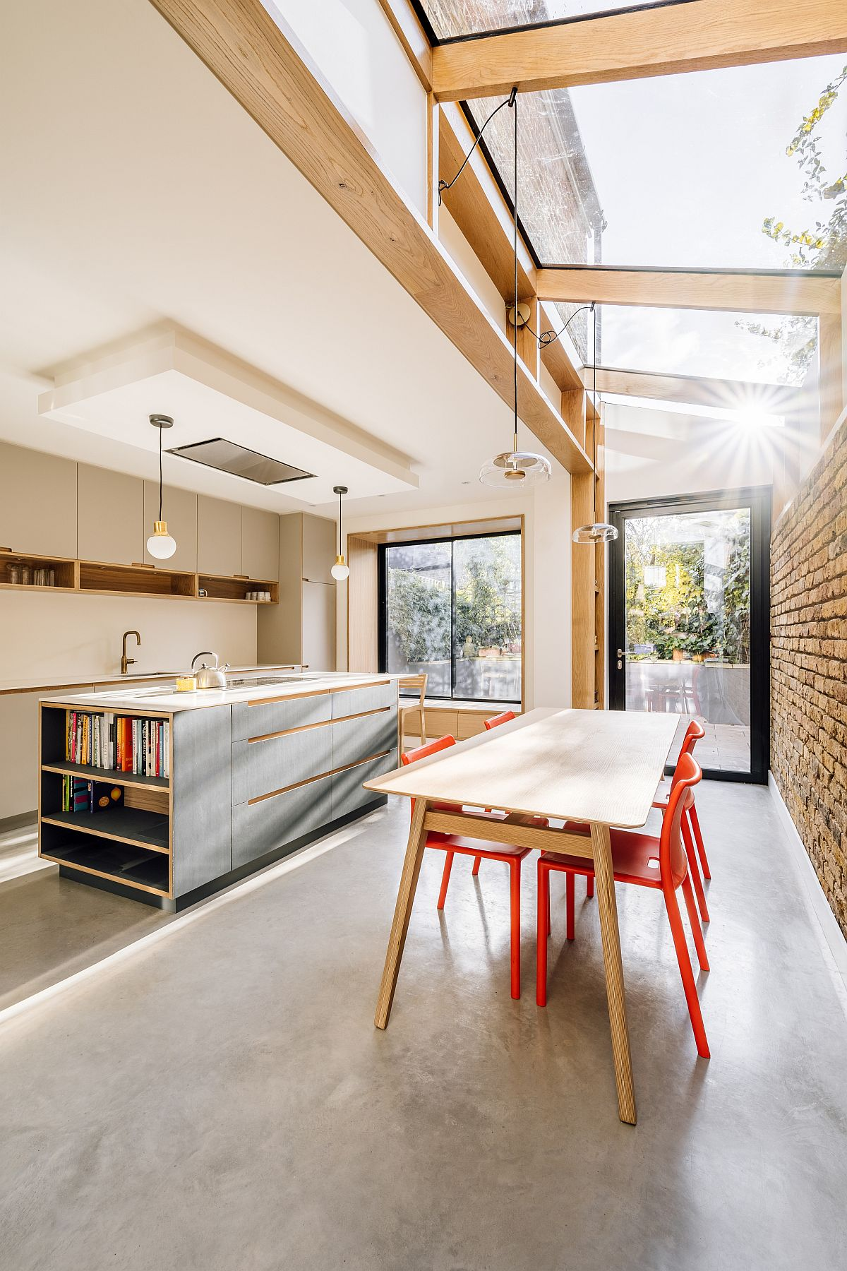 Exquisite modern kitchen with dining space is beautifully lit by the large sky light above