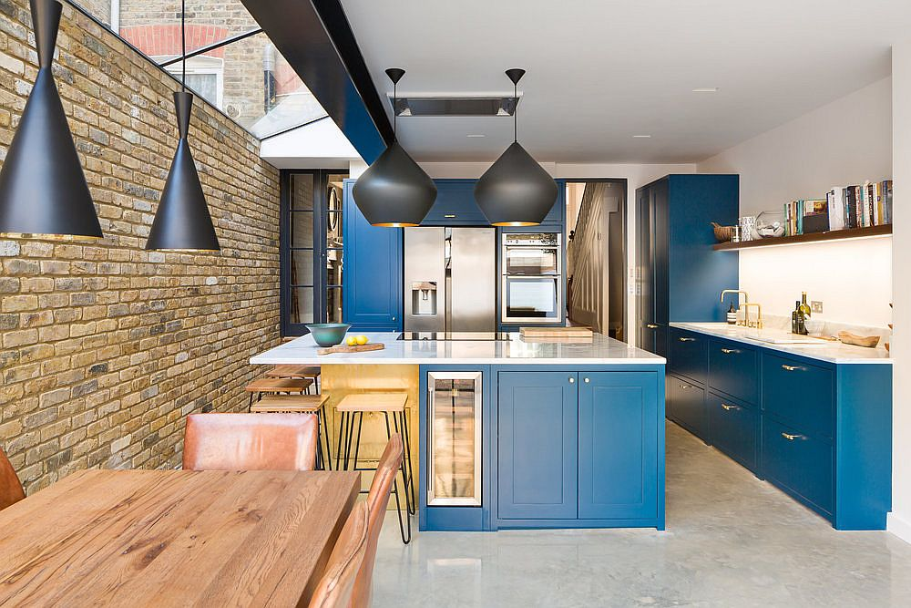 Fabulous contemporary kitchen in navy blue, white and brick with sparkling brass handles thrown into the mix!