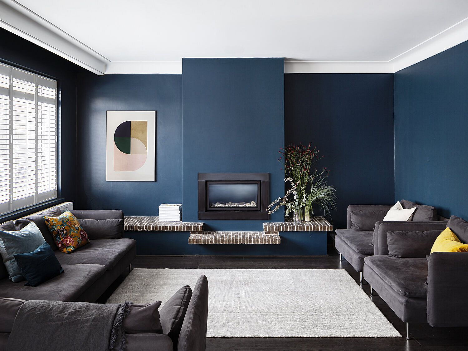 Fabulous dark blue living area with comfortable dark gray sofas and a small fireplace