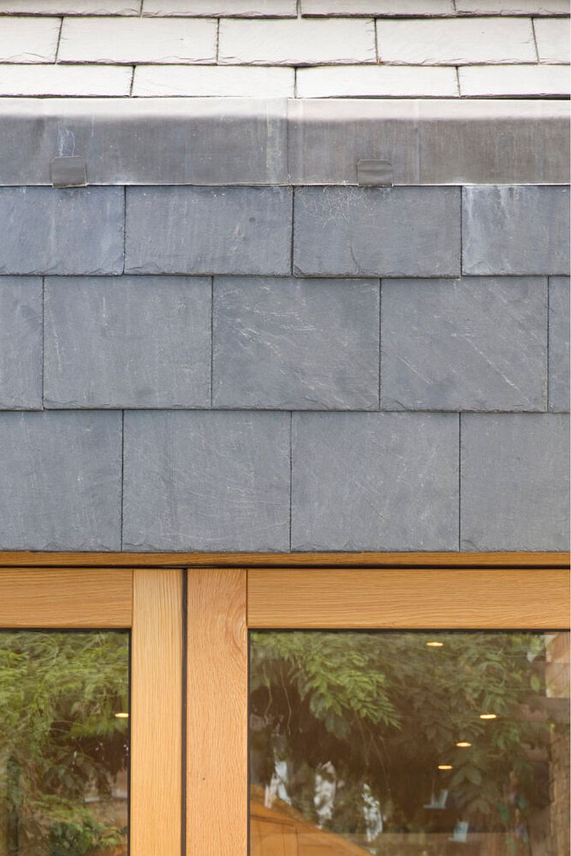 Gray tiles along with wood and glass shape this narrow London home on the outside