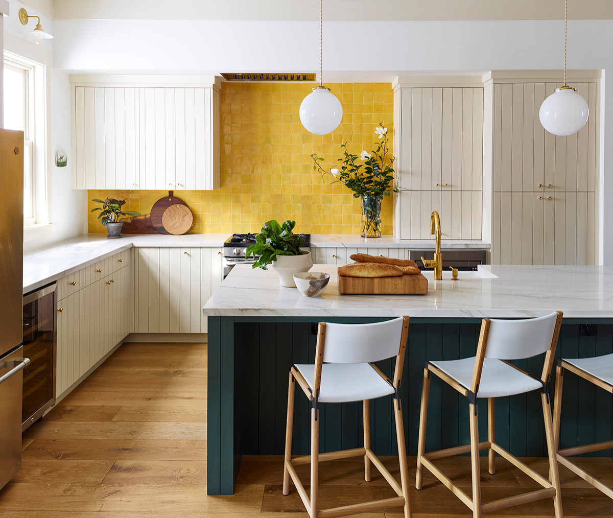 Kitchen island brings deep dark green to the kitchen while the backsplash pours in yellow