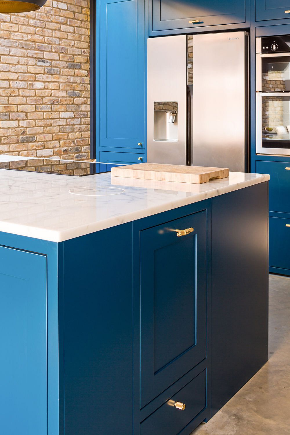 Kitchen island in navy blue with white marble countertop and brass handles for the cabinets