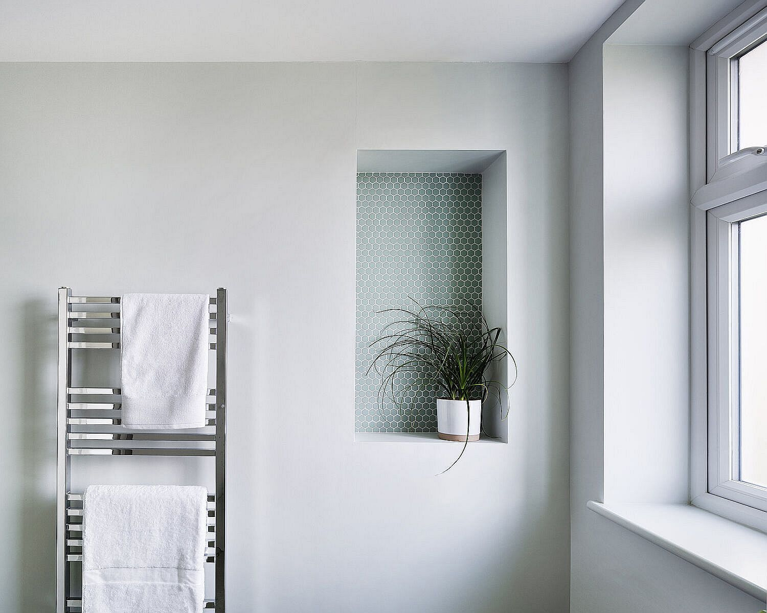 Little accent feature for the white modern bathroom with penny tiles and an indoor plant