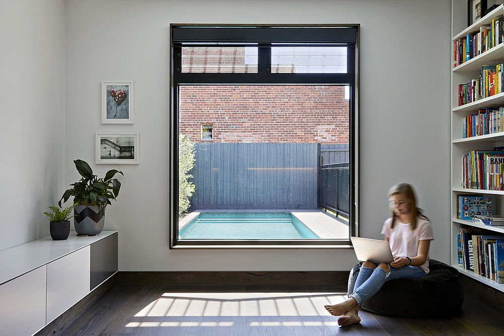 Lovely sitting area and library with large window that connects the interior with the pool area outside