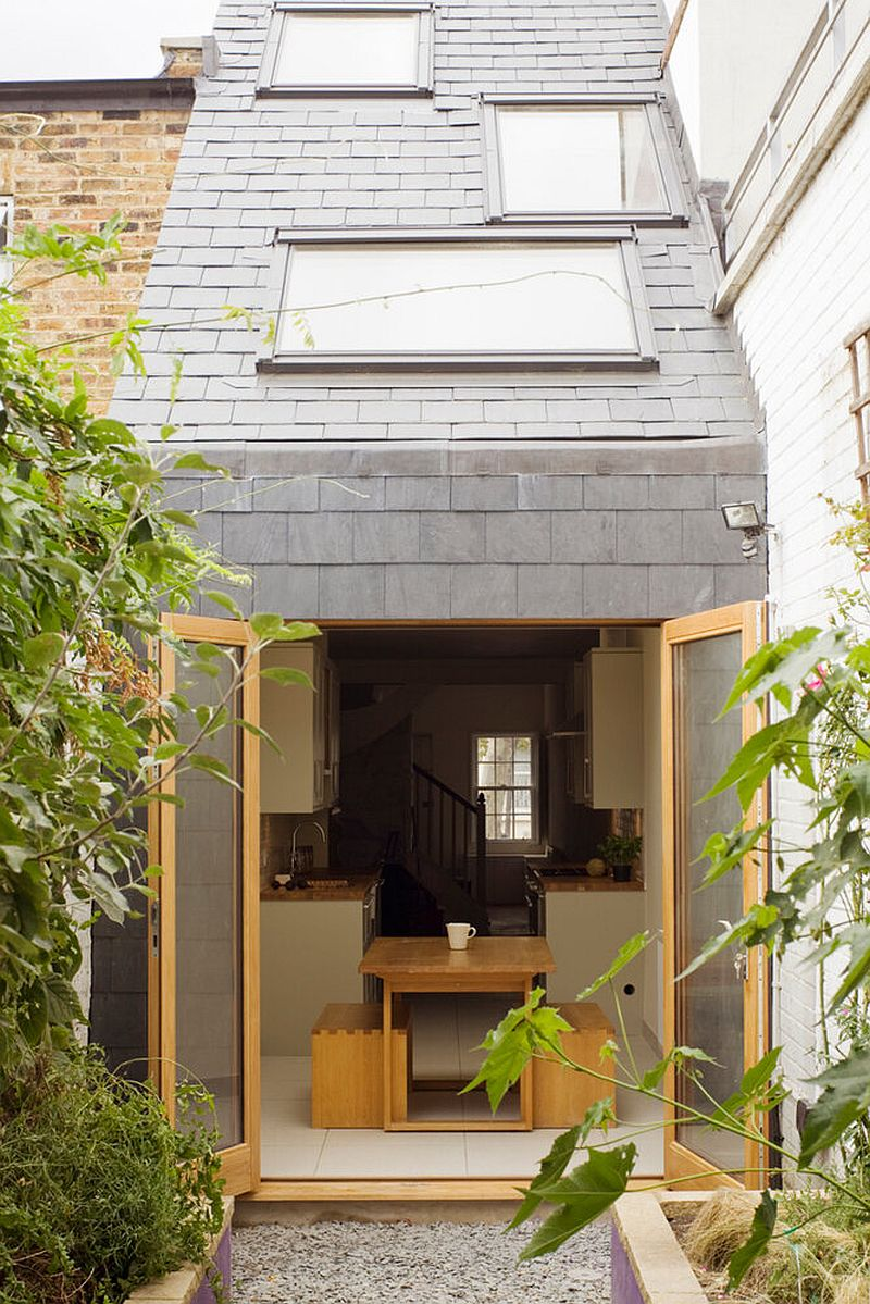 Modern Slim House in London with a gray and wood exterior and a sloped ceiling that has staggered skylight