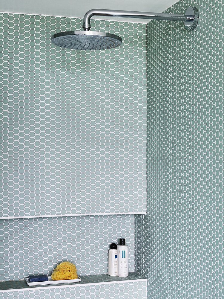 Modern bathroom shower area with penny tiles in pastel green