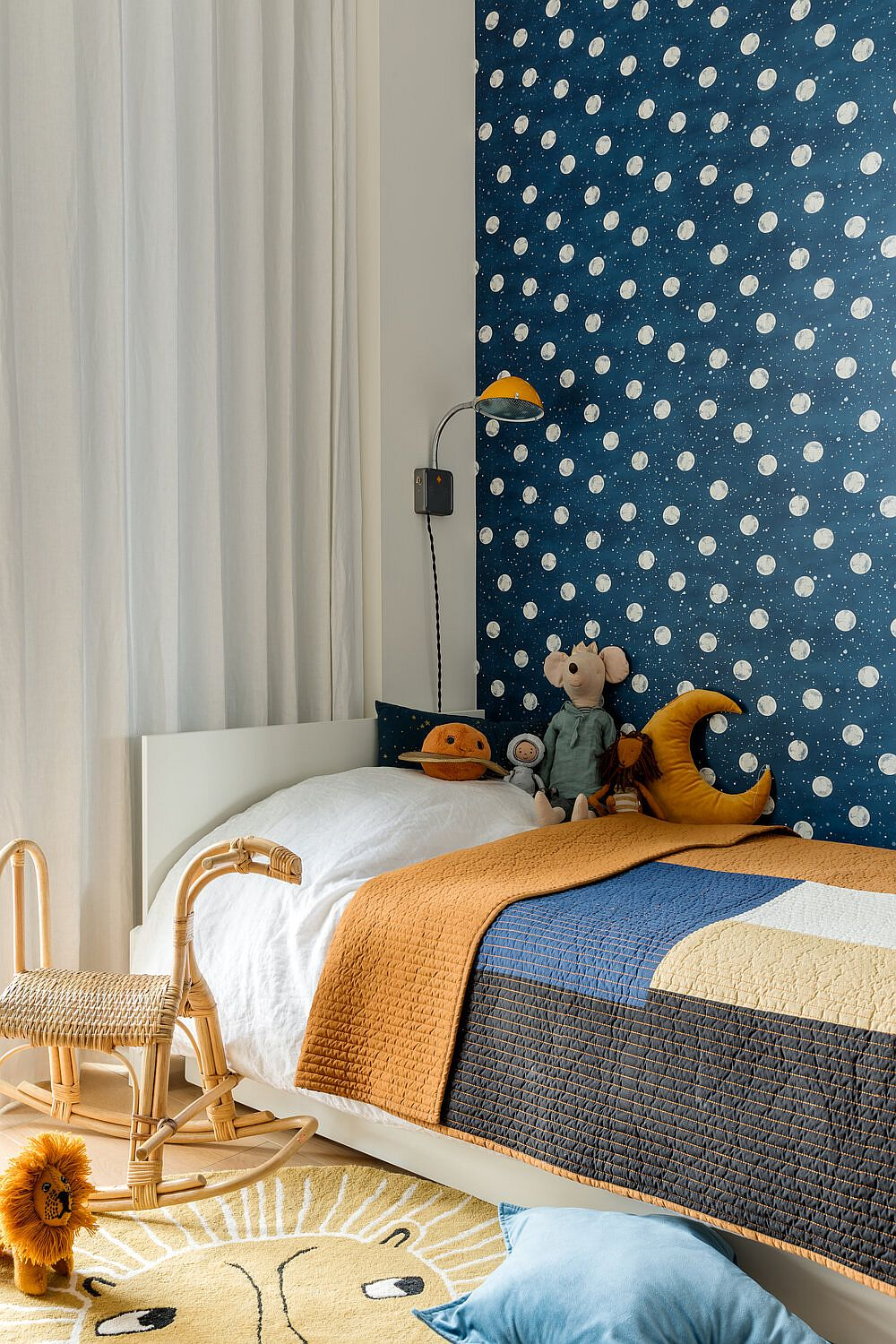 Modern kids' room with colorful backdrop in blue that features polka dot pattern