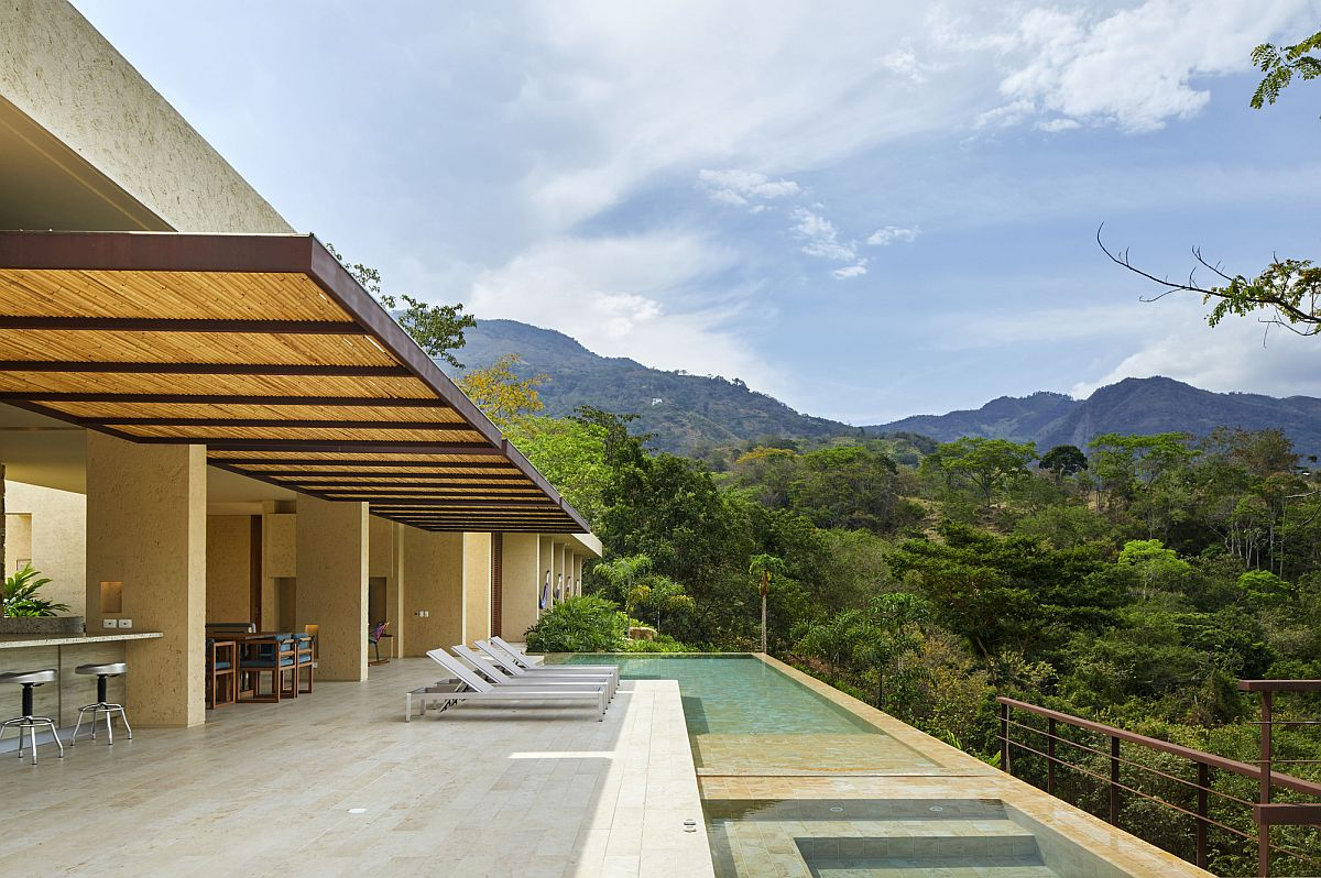 Pavilion-style kitchen, dining area and living space of the house become one with the pool and the deck