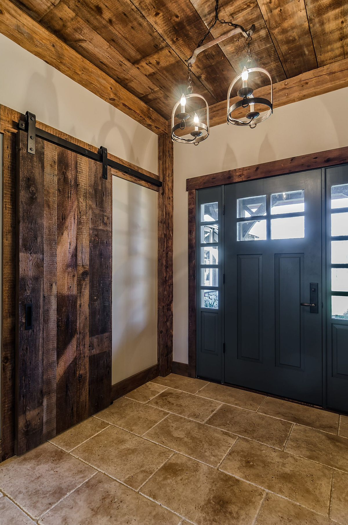 Reclaimed wood ceiling is coupled with a gorgeous sliding barn door to create a dashing modern rustic entry for this New York home