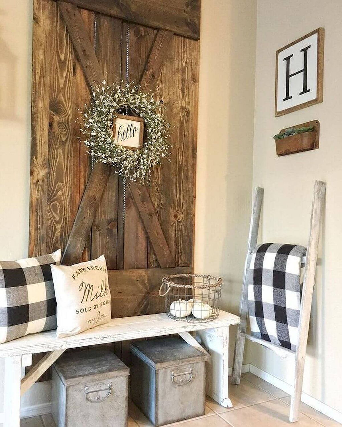 Reclaimed wooden bench and old barn door are used to decorate this modern rustic entryway