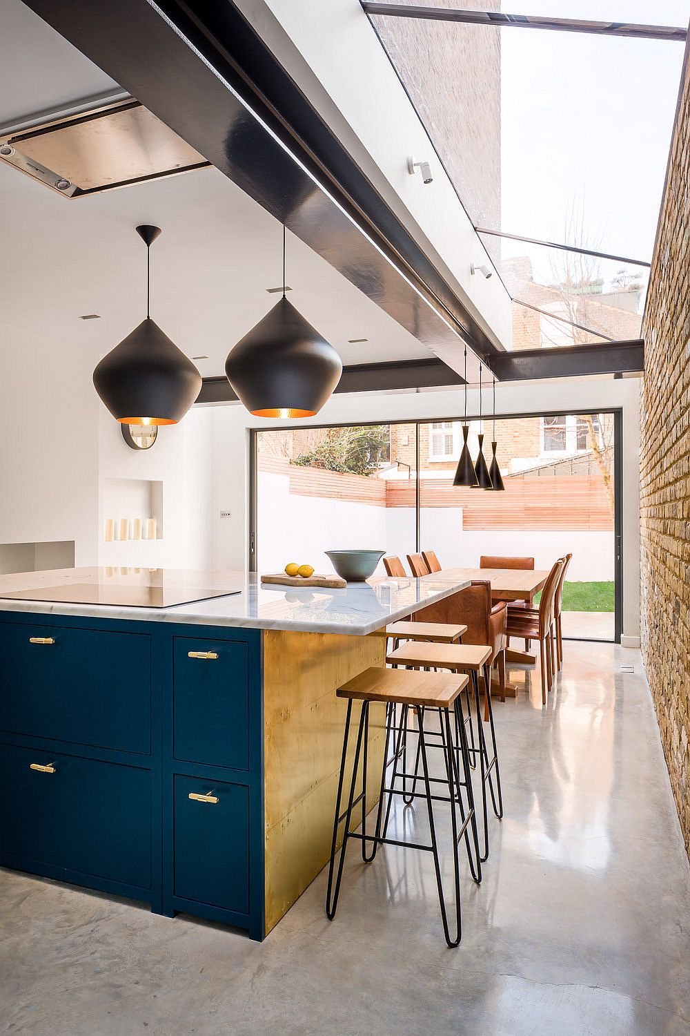 Skylight, glass doors bring natural light into this kitchen and dining area while Tom Dixon pendants take over after sunset