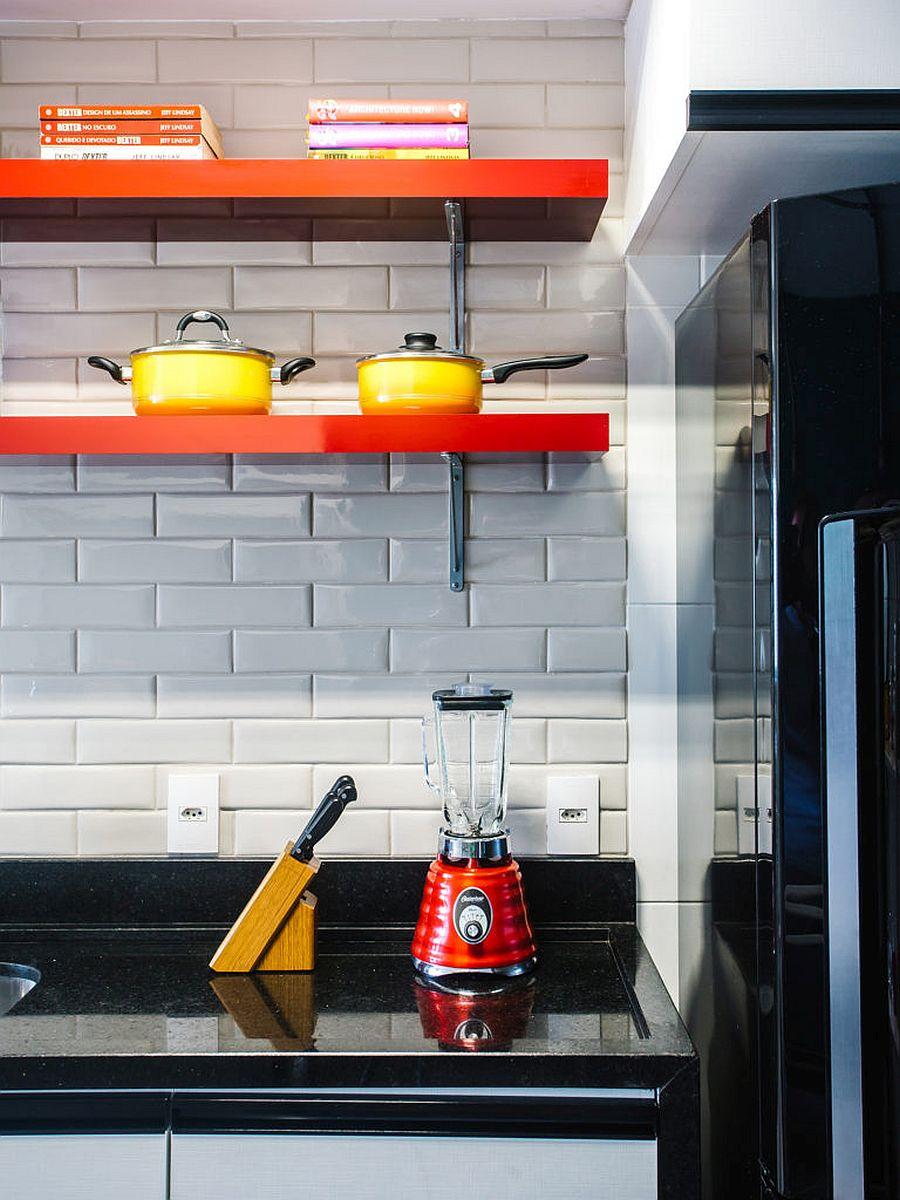 Sleek floating shelves in orange add color to the white-tiled kitchen backsplash