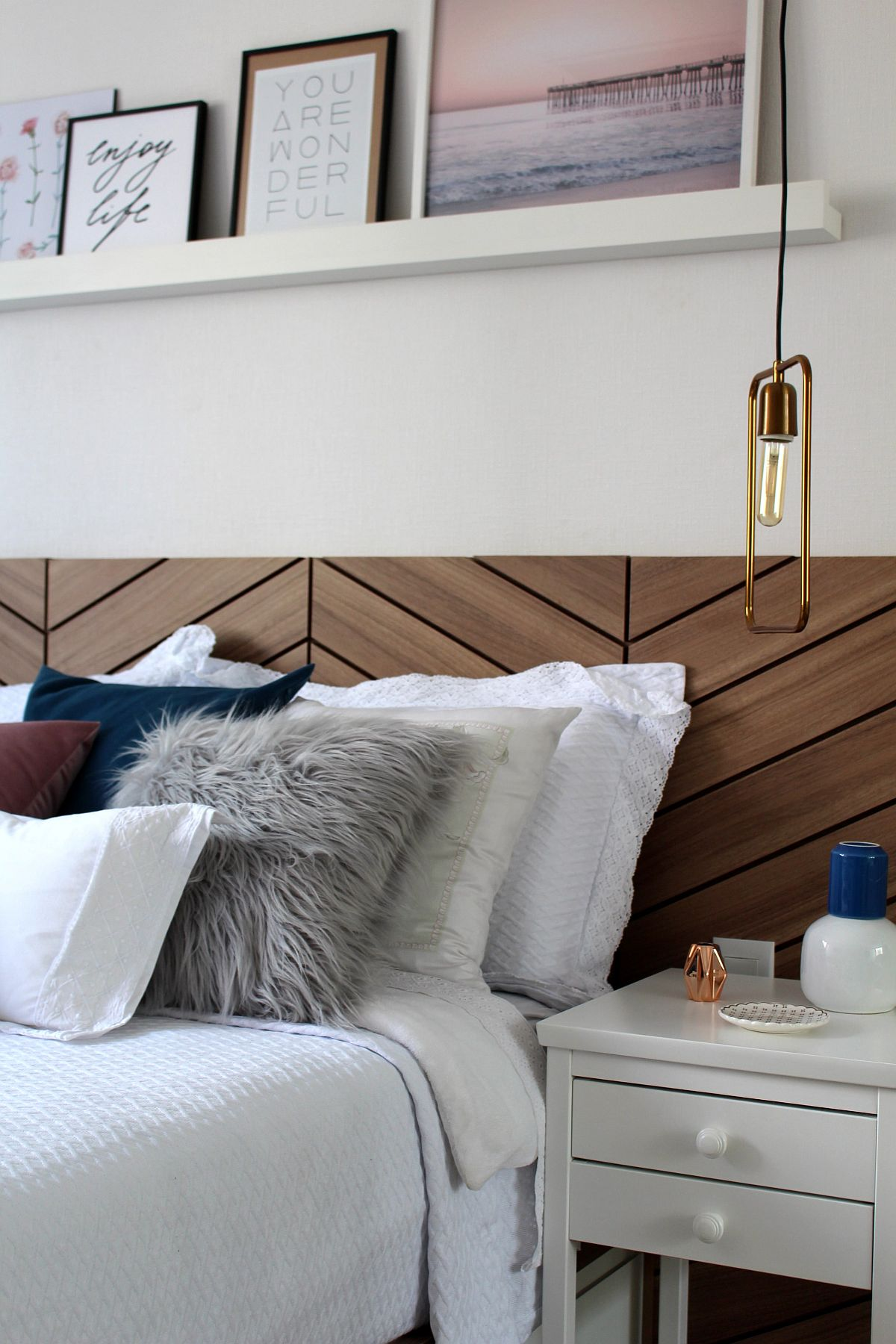 Slim bedside lighting with metallic glitz brings contrast to the modern wood and white bedroom