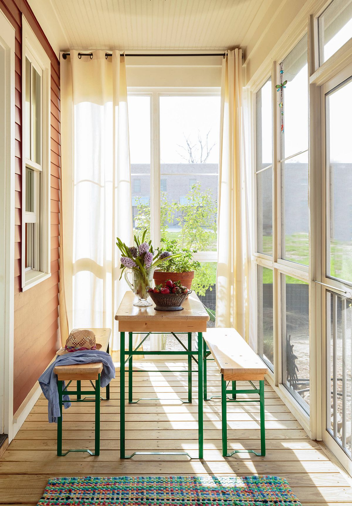 Slim screened porch becomes sunroom with smart and innovative decor and just a hnt of color