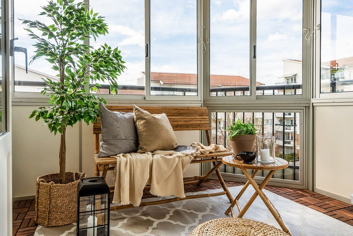 Small Scandinavian sunroom of Stockholm apartment with a bench creates the perfect atmosphere for picnic at home