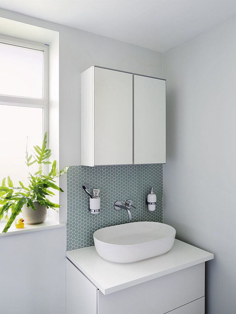Small vanity in the corner along with medicine cabinet saves space