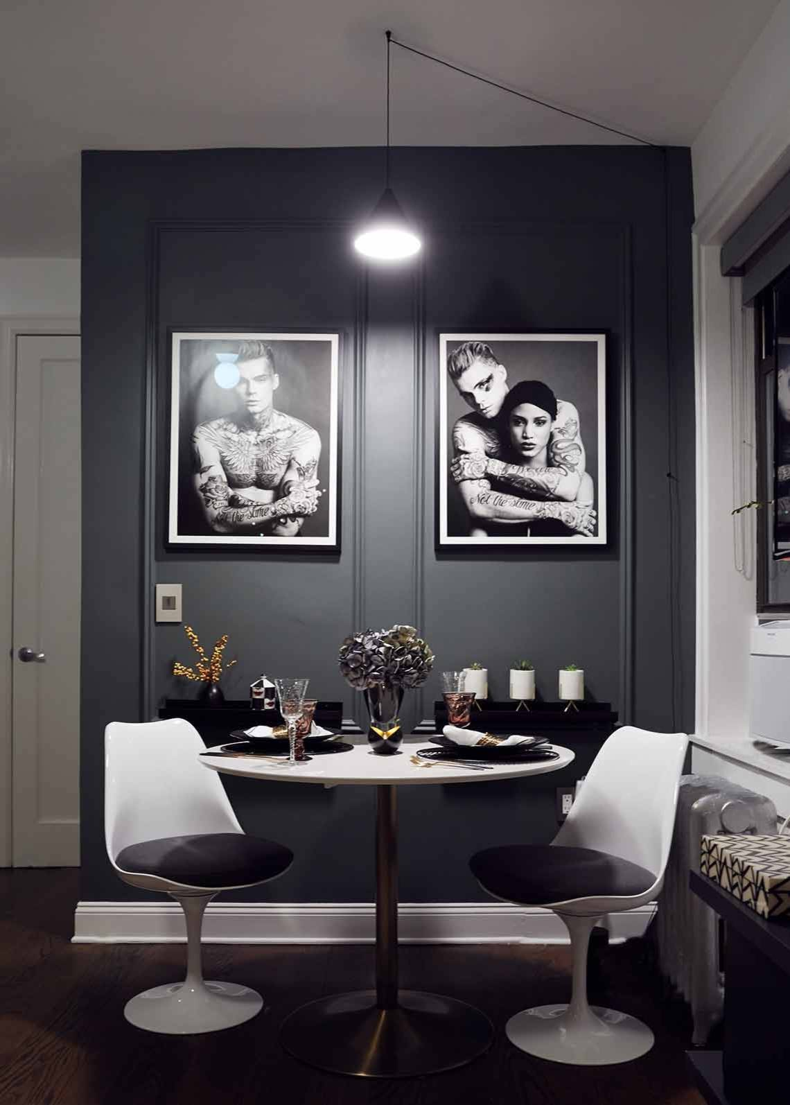 Sophisticated NYC dining room with dark gray walls and framed photographs in the backdrop
