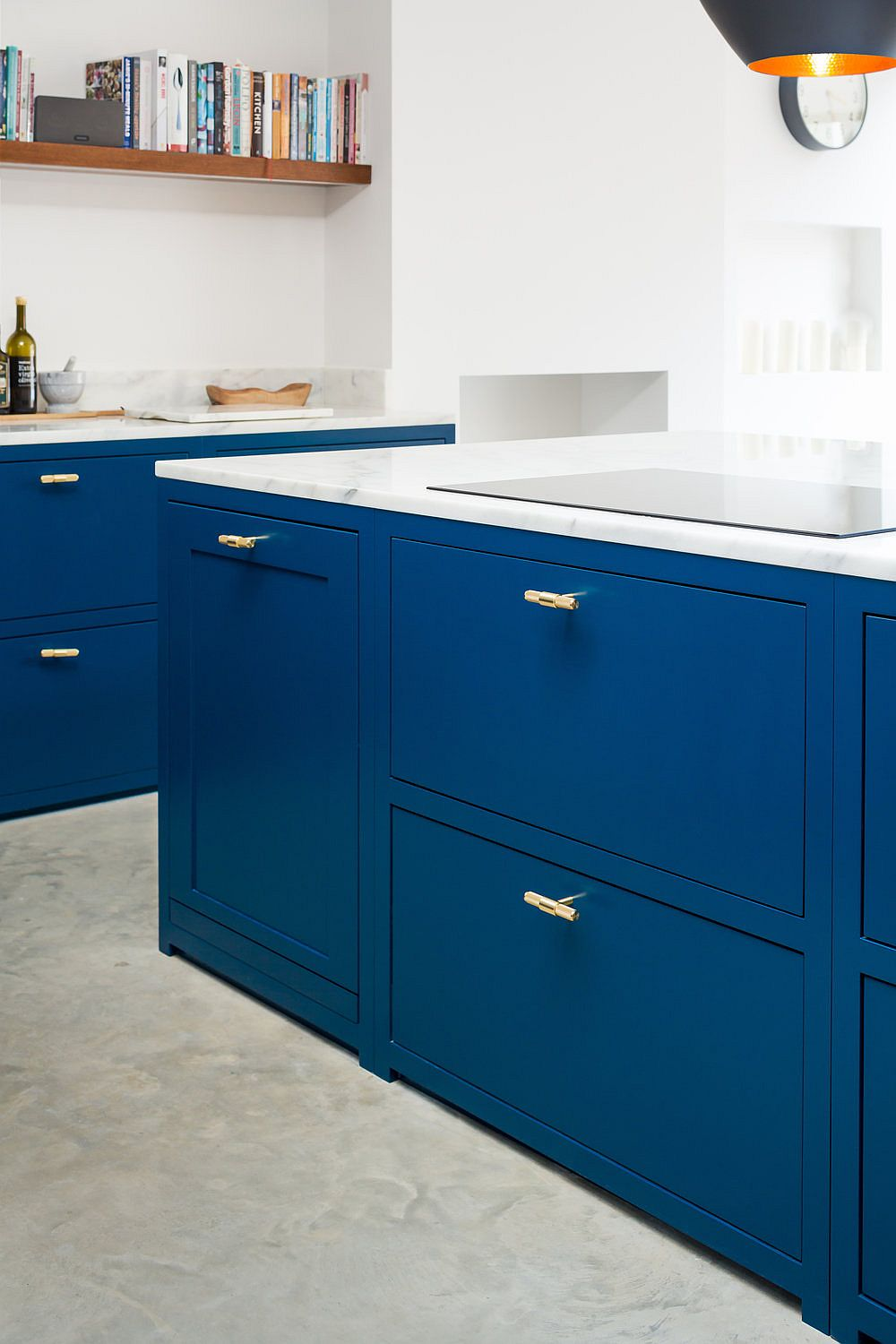 Space-savvy and stylish modern kitchen island with navy blue joinery and brass handles