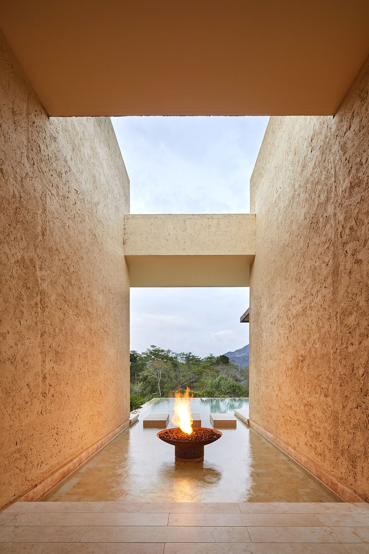 Stone walls that create entry to the pool deck create the illusion of fire and water at the house