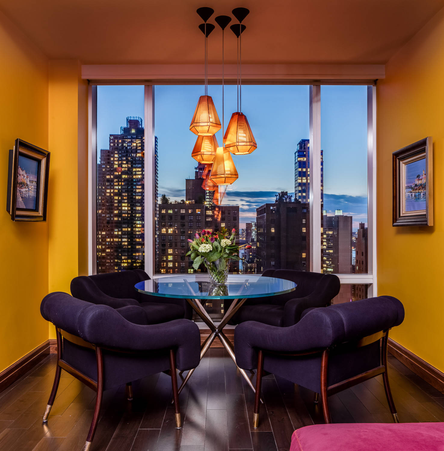 Stunningly beautiful dining room of apartment near Central Park in NYC with captivating views of the city and bright yellow walls
