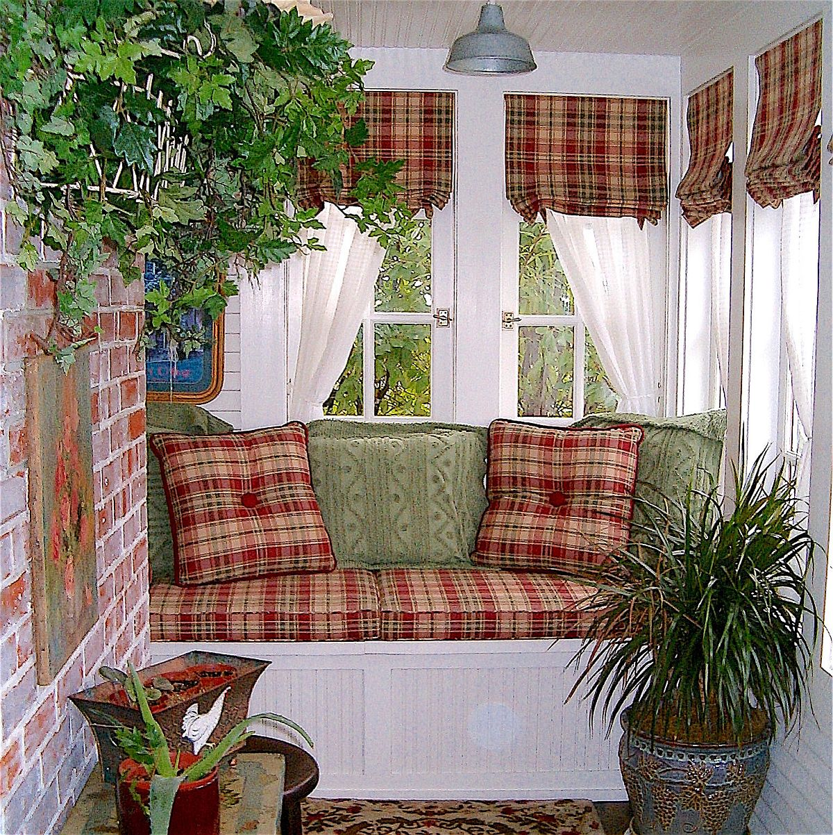 Textiles with plaid pattern add both color and authentic farmhouse appeal to the small sunroom