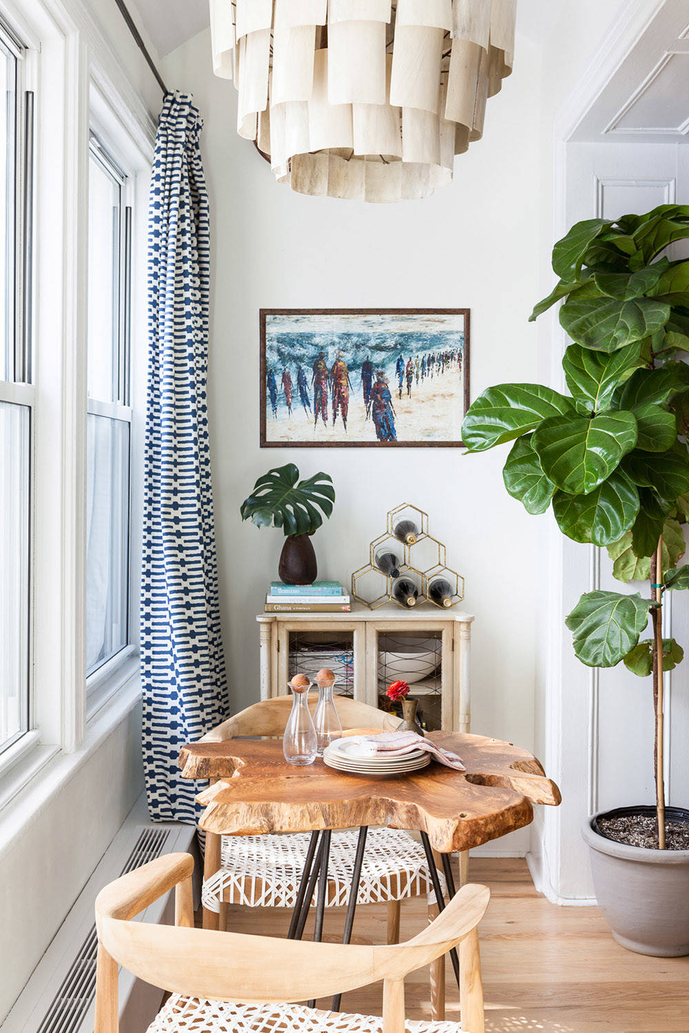 Tiny eclectic dining space inside the small NYC apartment that offers a view of the city skyline outside