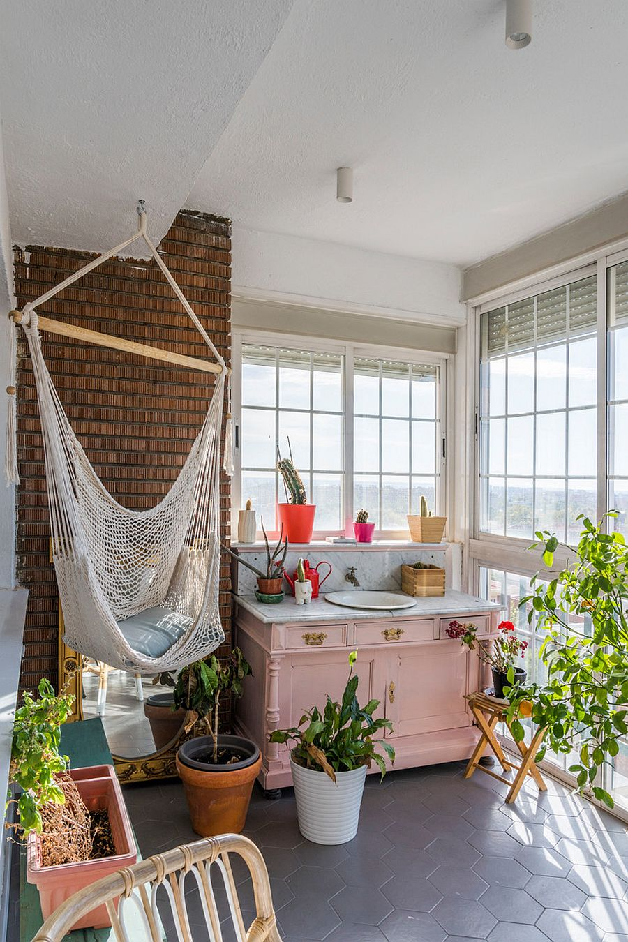 Tiny shabby chic sunroom with bright pops of color and a hammock in the corner